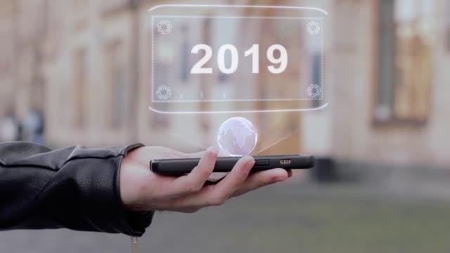 vídeos de stock, filmes e b-roll de mãos de machos mostram no smartphone conceitual holograma de hud 2019 - manipulação digital