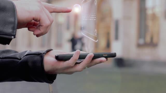stockvideo's en b-roll-footage met mannelijke handen toon op smartphone conceptuele hud hologram reclame - lood