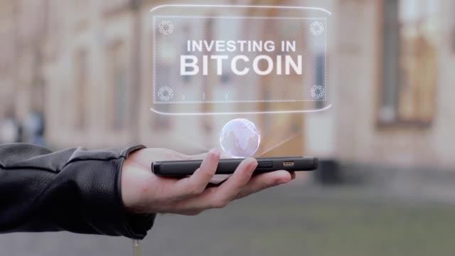 vídeos de stock, filmes e b-roll de mãos masculinas mostram no smartphone conceitual holograma de hud investindo em bitcoin - manipulação digital