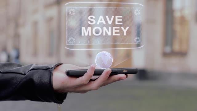 vidéos et rushes de voir la mains mâle sur smartphone conceptuel hologramme de hud économisez de l'argent - abaisser