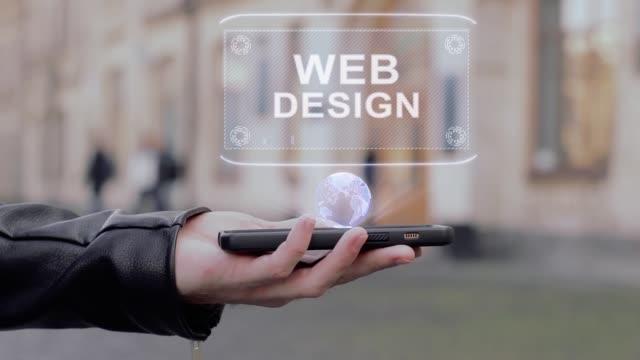 vídeos y material grabado en eventos de stock de manos masculinas muestran en smartphone holograma de hud conceptual diseño web - seo