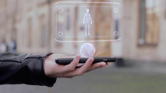 スマート フォン概念 hud ホログラム女性体に男性の手を表示します。 - ホログラム点の映像素材/bロール