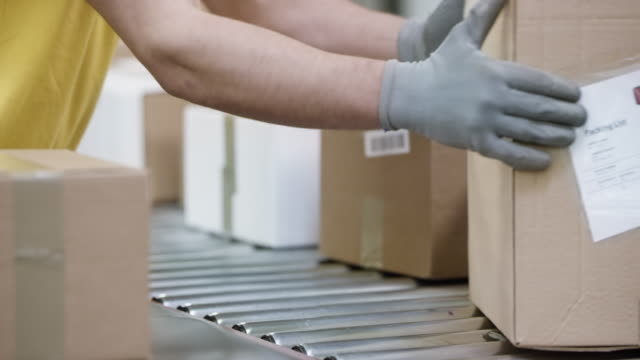 Male hands sorting packages on the conveyor belt