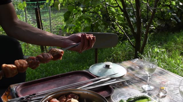 Male hands take raw meat shish kebab and put it on metal skewers
