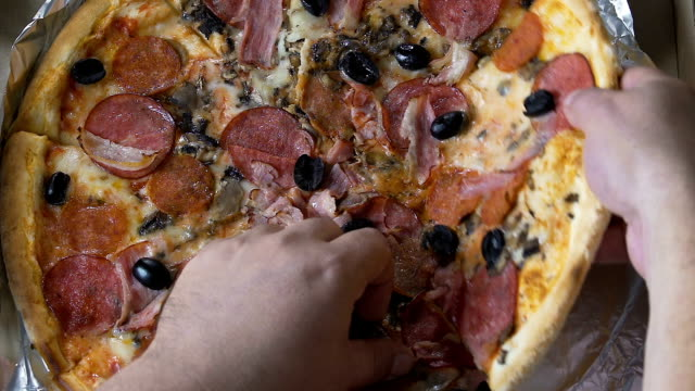 Male hands taking big huge pizza slice from box, weight gain, stress eating video