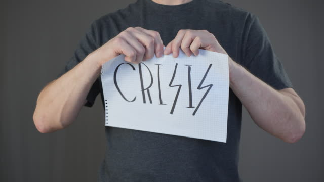 Male hands tearing paper with crisis sign on checkered paper slow motion on grey background. Finished financial crisis. Stop economic problems.