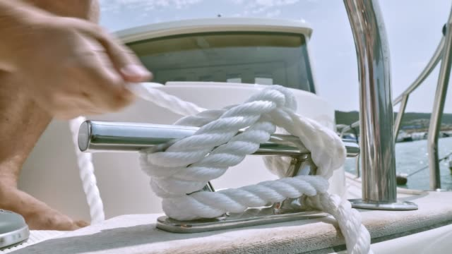 male hands tying a knot to the cleat on the boat - annodare video stock e b–roll