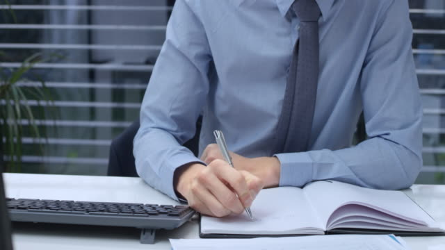 DS Male hands typing on the keyboard and writing notes into a notepad in the office