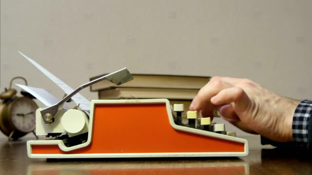 Male hands typing on the old red typewriter at the desk with books - video