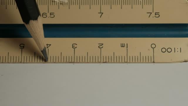 manliga händer med hjälp av en triangulär skala linjal. - mätinstrument bildbanksvideor och videomaterial från bakom kulisserna