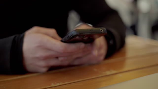 Male hands using smartphone above wooden table