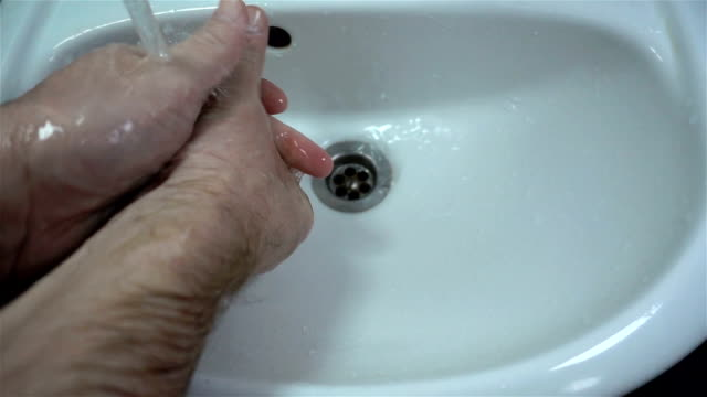 Male hands wash in the sink in slow motion. Male hands wash with water in the sink in slow motion. Hand disinfection household fixture stock videos & royalty-free footage