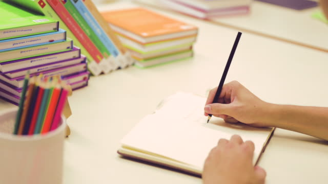 Male hands write something on the book to prepare for work in the library, Success and strategy concept. Jigsaw, Plan, Library, Puzzle, Education, Lifestyle concept. 4K.