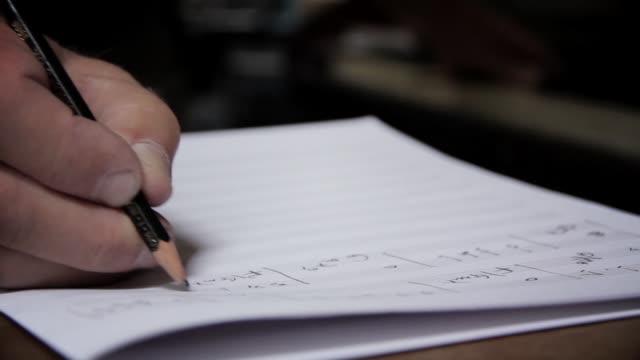 vídeos de stock e filmes b-roll de male hands writing music notes with pencil. - compositor