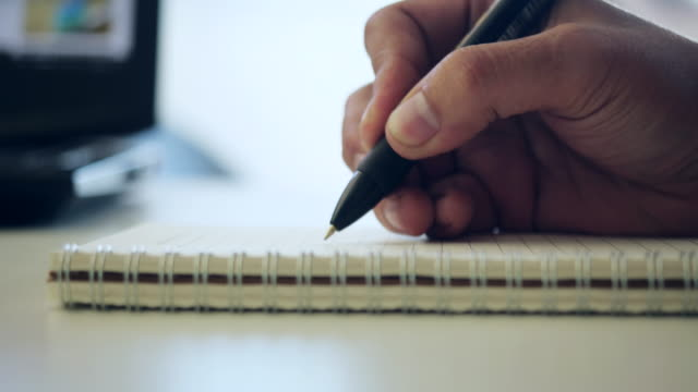 stockvideo's en b-roll-footage met een mannelijke handen schrijven op een stuk papier. schrijven van brieven. - schrijven