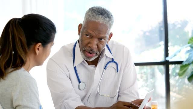manlig hälsa professionell förklarar ett internet försäkringsformulär för patienten - patient bildbanksvideor och videomaterial från bakom kulisserna