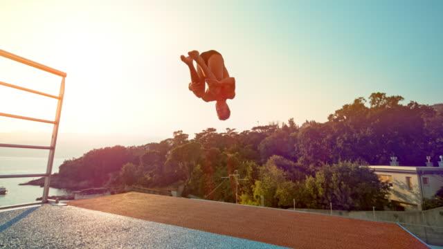 slo mo männliche hohe taucher tun einen flip und springen von der plattform bei sonnenuntergang - nackter oberkörper stock-videos und b-roll-filmmaterial