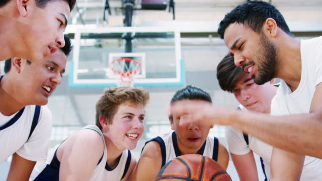 Male High School Basketball Players Joining Hands On Ball During Team Talk With Coach Male high school basketball team joining hands on ball after motivational talk with coach - shot in slow motion high school sports stock videos & royalty-free footage