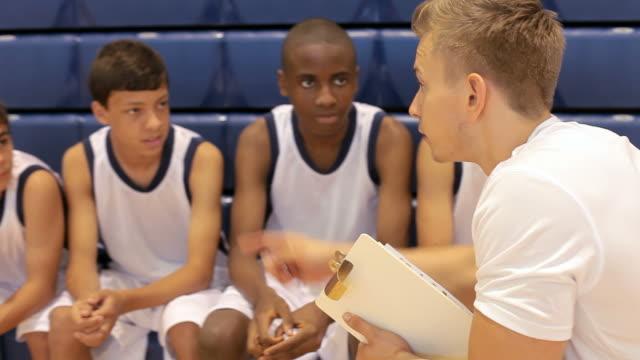 El equipo de básquetbol masculino de la escuela que hable con entrenador del equipo - vídeo