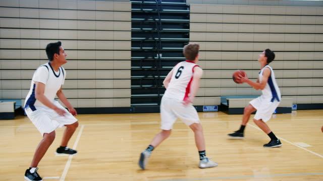 Male High School Basketball Team Scoring Basket On Court And Celebrating Male high school basketball team shooting and scoring basket during match - shot in slow motion high school sports stock videos & royalty-free footage