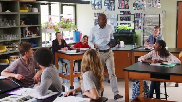 生物学のクラスで男性高校教師教育生 ビデオ