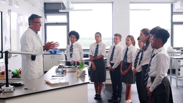 mężczyzna high school tutor nauczanie uczniów noszenie mundurki w klasie nauki - uniform filmów i materiałów b-roll
