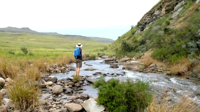 Male hiker admires the river flowing through the valley A male hiker enjoys the views over river flowing through the valley near Kwa-Zulu Natal, South Africa natal stock videos & royalty-free footage