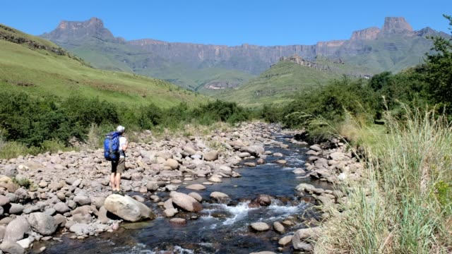 Male hiker admires the view over the Tugela River A male hiker enjoys the views over The Tugela river flowing from the might Amphitheatre and the Drakensberg Mountains, Kwa-Zulu Natal, South Africa natal stock videos & royalty-free footage