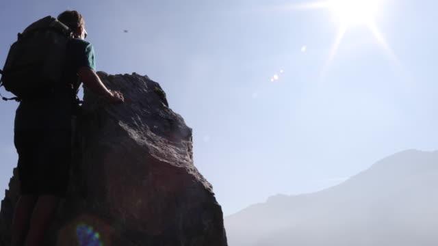 vidéos et rushes de randonneur mâle monte pour pinnacle sommet au lever du soleil - évasion du réel