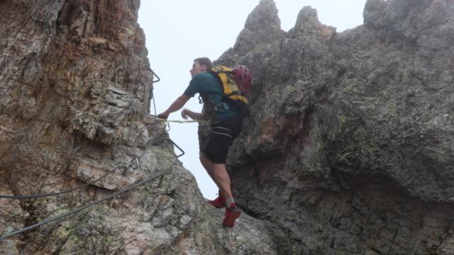 vidéos et rushes de randonneur mâle monte vertical par voie ferrata en brume - évasion du réel