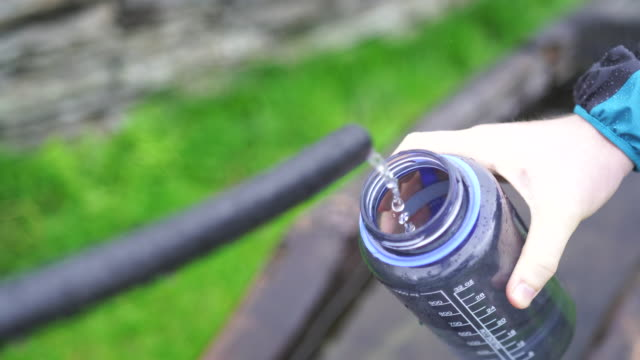 Male hiker fills up water bottle from fresh water fountain in mountains Exploring the mountains of Ticino, Switzerland filling stock videos & royalty-free footage