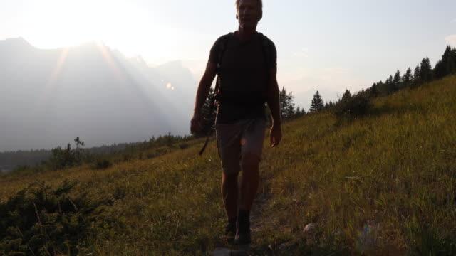 vidéos et rushes de randonneur mâle suit le sentier sur la crête de ridge meadow, lever du soleil - un seul homme d'âge mûr