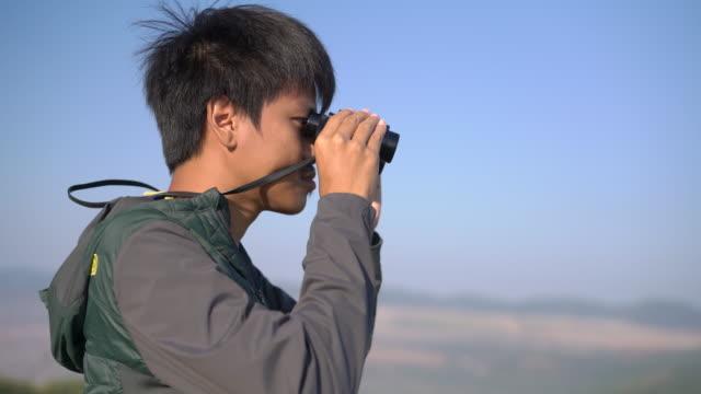 双眼鏡を通して自然の景色を眺めている男性ハイカー - バードウォッチング点の映像素材/bロール