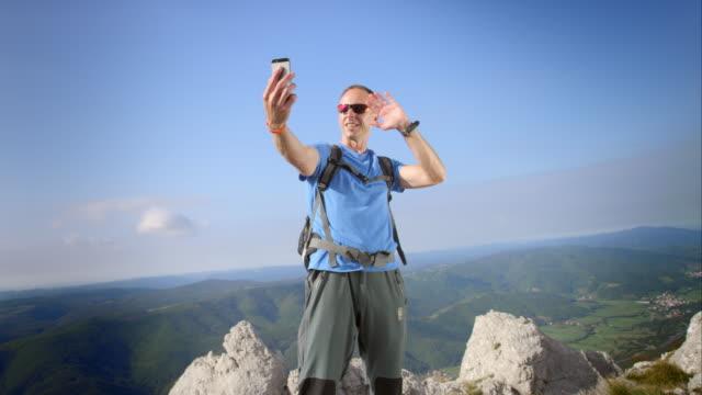 Homme de randonnée dans une vidéo appeler au sommet de la montagne - Vidéo