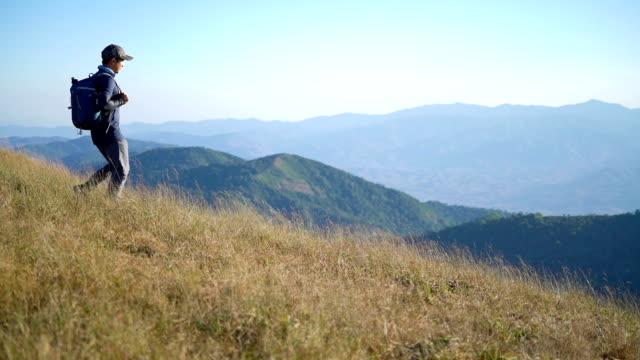 slo mo male hiker on top of the mountain - ekoturystyka filmów i materiałów b-roll