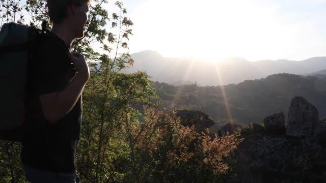 vídeos de stock, filmes e b-roll de alpinista masculino pausas acima vale e as montanhas ao nascer do sol - camiseta preta