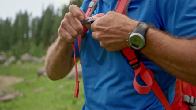 Male hiker putting on his backpack and securing the straps Medium handheld shot of a male hiker putting on his backpack and tightening the straps. Shot in Slovenia. wristwatch stock videos & royalty-free footage