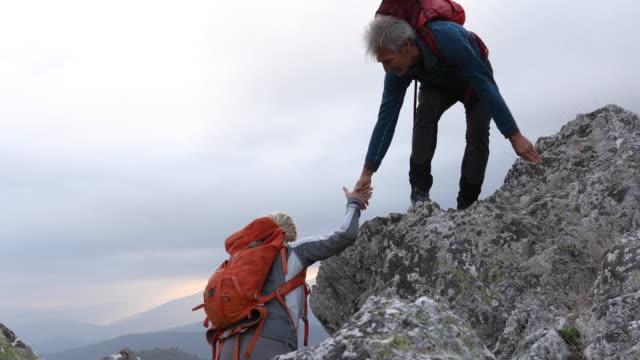 vídeos de stock e filmes b-roll de male hiker reaches hand down to female companion - 55 59 anos