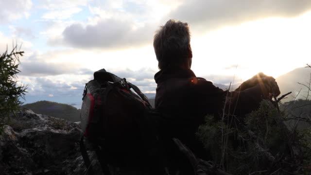 vidéos et rushes de randonneur mâle détend au-dessus des montagnes au lever du soleil - un seul homme d'âge mûr