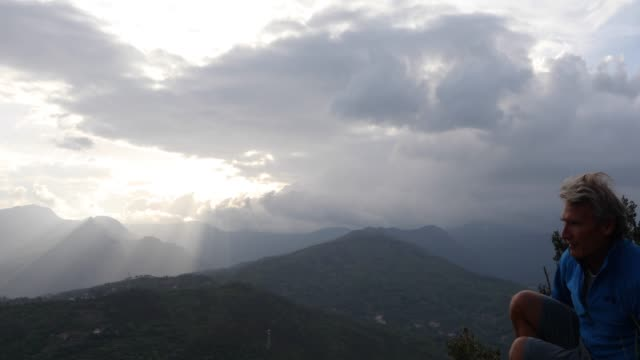 male hiker relaxes above valley and mountains on stormy day - solo un uomo maturo video stock e b–roll