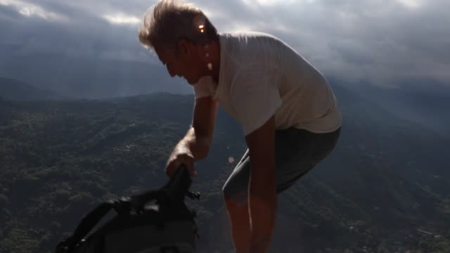 male hiker relaxes on rock ledge above mountains and valley at sunrise - solo un uomo maturo video stock e b–roll