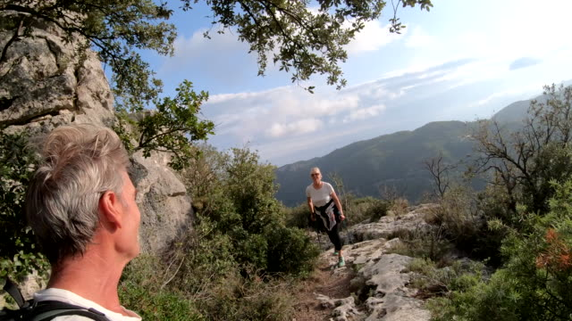 male hiker traverses ridge crest above mountains, valley - cinquantenne video stock e b–roll
