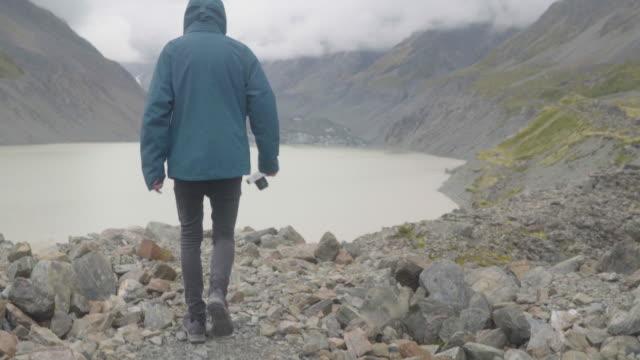 stockvideo's en b-roll-footage met mannelijke wandelaar die onderaan een rotsachtige heuvel in nieuw zeeland loopt - minder dan 10 seconden