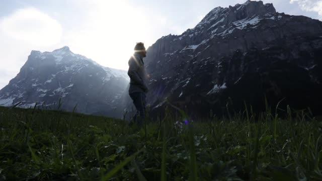 male hiker walks towards mountains at sunrise - solo un uomo maturo video stock e b–roll