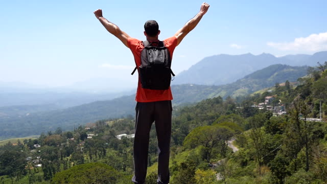 Male hiker with backpack reaches up top of mountain and outstretched arms up. Young traveler jogs to the edge of canyon and raises hands up. Man tourist enjoys beautiful picturesque landscape.