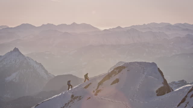 Male hikers climbing snowcapped mountain