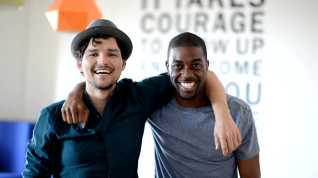 Male Hipster Best Friends African American and Hispanic male best friends with arms around each other looking in camera. The loft type space. has a saying painted on the wall
