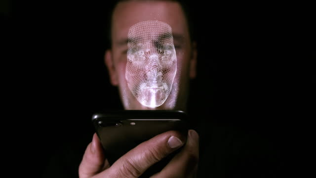 Male holding a digital device with a 3D imprint of his face as a hologram. Facial recognition and identity concept video