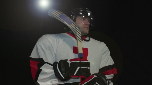 Male Ice Hockey Player Portrait pose - Super Slow Motion 180 degree rotation Stock HD video clip footage of a male Ice Hockey Player. Filmed in Super Slow motion, the camera rotates 180 degrees around the player. Black Background. Indoors pre game stock videos & royalty-free footage
