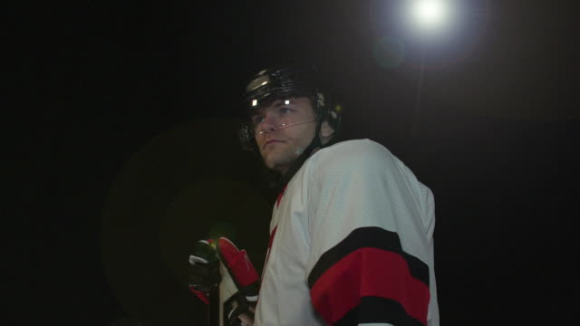 Male Ice Hockey Player Portrait - Super Slow Motion 180 degree rotation Stock HD video clip footage of a male Ice Hockey Player. Filmed in Super Slow motion, the camera rotates 180 degrees around the player. Black Background. Indoors pre game stock videos & royalty-free footage